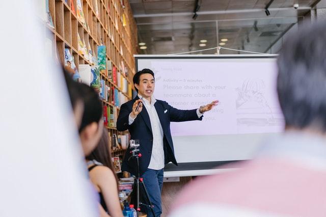 man doing a presentation standing beside projector screen IT tech support pexels